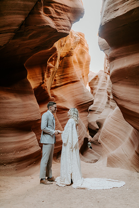bride in an ivory long gown with bellowing sleeves and a boho design, groom in a light grey suit, exchanging vows in the caves