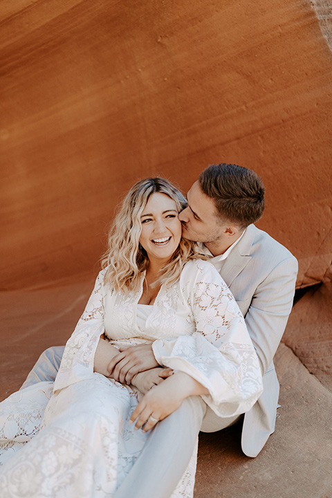 bride in an ivory long gown with bellowing sleeves and a boho design, groom in a light grey suit, sitting in the caves