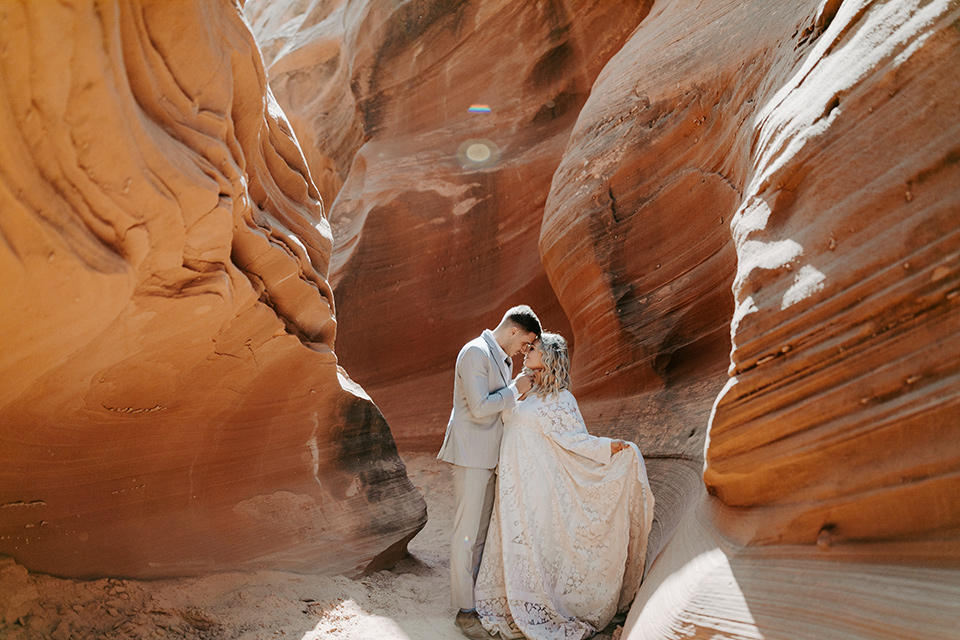 bride in an ivory long gown with bellowing sleeves and a boho design, groom in a light grey suit at entrance on the caves