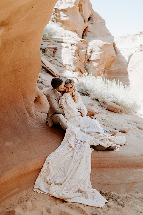 bride in an ivory long gown with bellowing sleeves and a boho design, groom in a light grey suit sitting