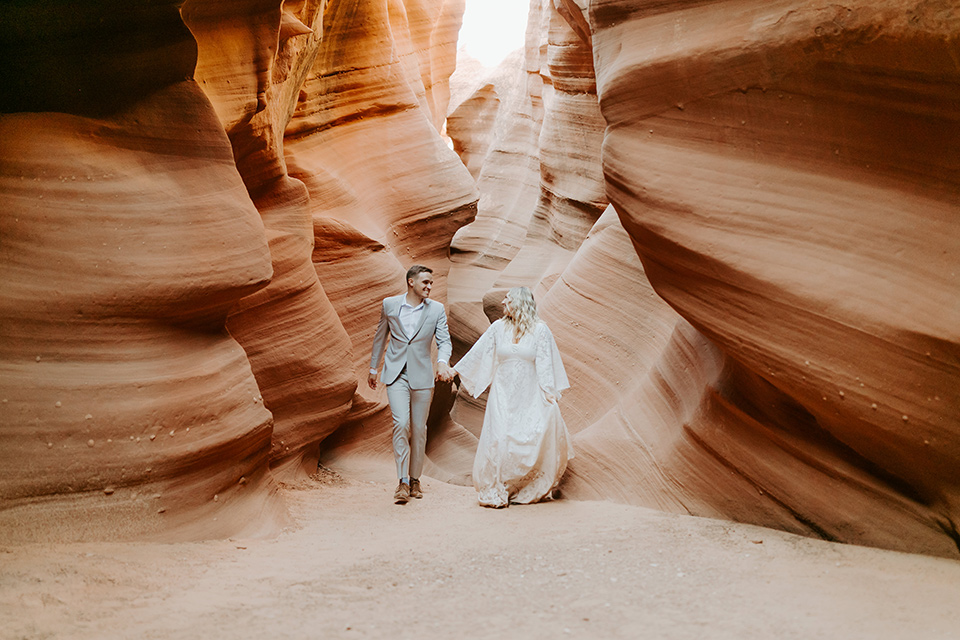 bride in an ivory long gown with bellowing sleeves and a boho design, groom in a light grey suit walking in the caves