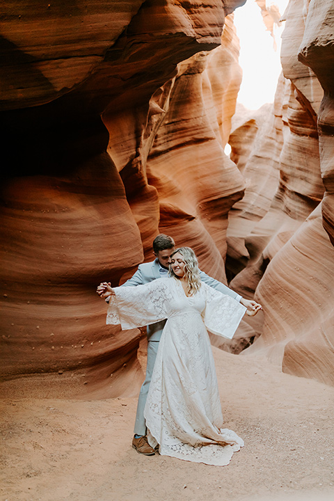 bride in an ivory long gown with bellowing sleeves and a boho design, groom in a light grey suit
