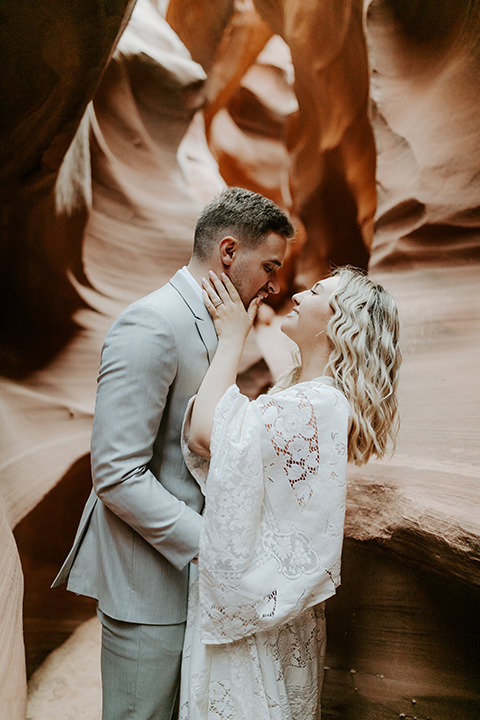 bride in an ivory long gown with bellowing sleeves and a boho design, groom in a light grey suit embracing