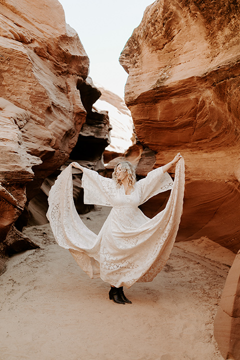 bride in an ivory long gown with bellowing sleeves and a boho design standing