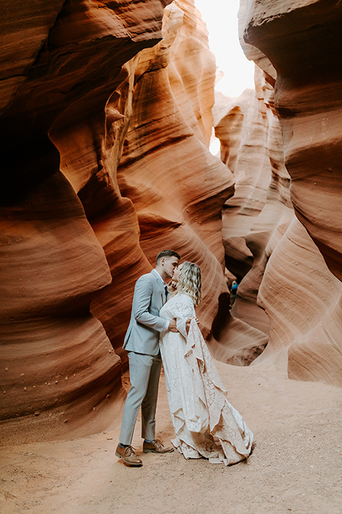 bride in an ivory long gown with bellowing sleeves and a boho design, groom in a light grey suit, in the caves kissing