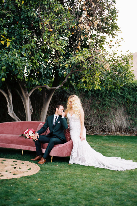bride in a vintage bohemian gown with beaded details and cape, groom in a green suit with a floral tie sitting on couch