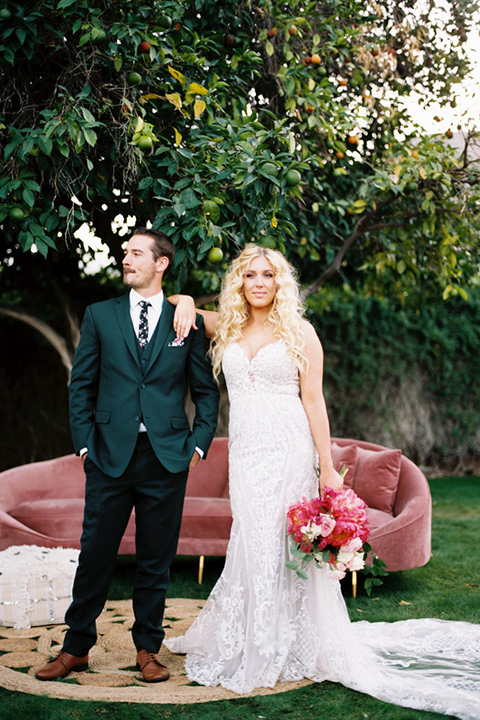bride in a vintage bohemian gown with beaded details and cape, groom in a green suit with a floral tie standing by the couch