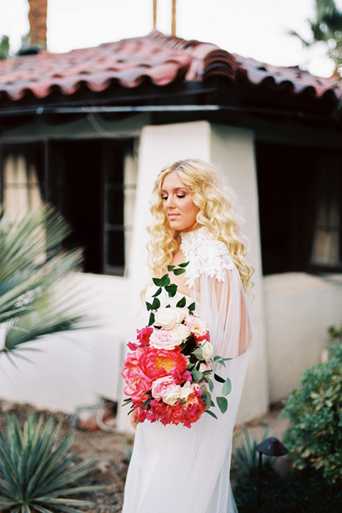 bride in a vintage bohemian gown with beaded details and cape