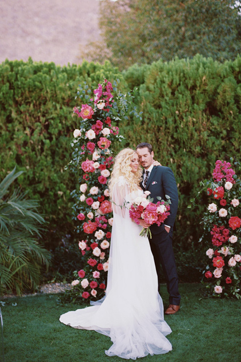 bride in a vintage bohemian gown with beaded details and cape, groom in a green suit with a floral tie at ceremony