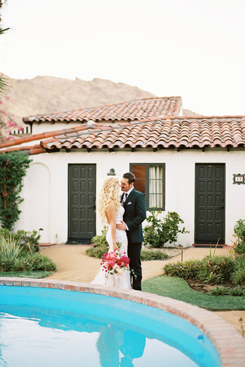 bride in a vintage bohemian gown with beaded details and cape, groom in a green suit with a floral tie by the pool