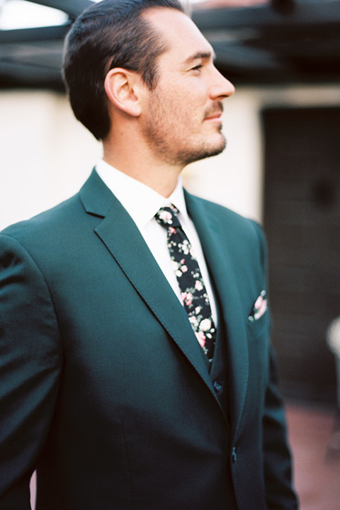 groom in a green suit with a floral tie