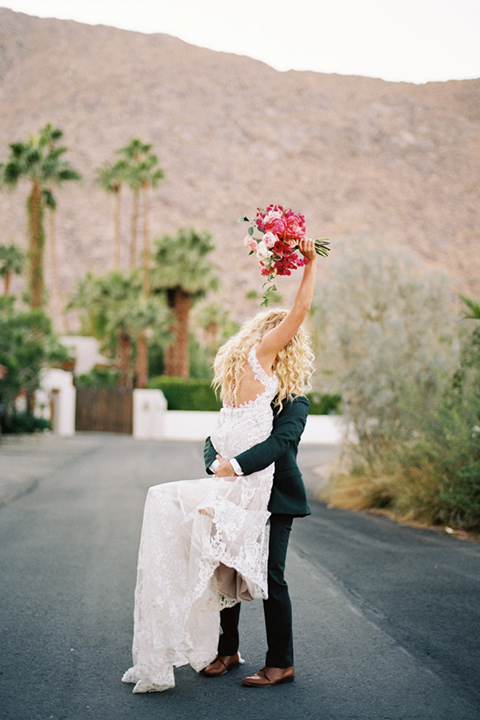 bride in a vintage bohemian gown with beaded details and cape, groom in a green suit with a floral tie
