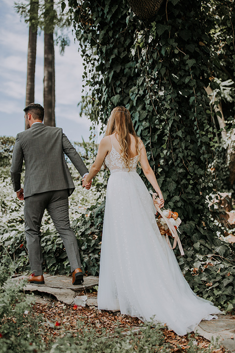 bride in a bohemian lace gown with a tulle skirt, lace boots, and headpiece and the groom in a café brown suit with an ivory tie, with a geometric arch