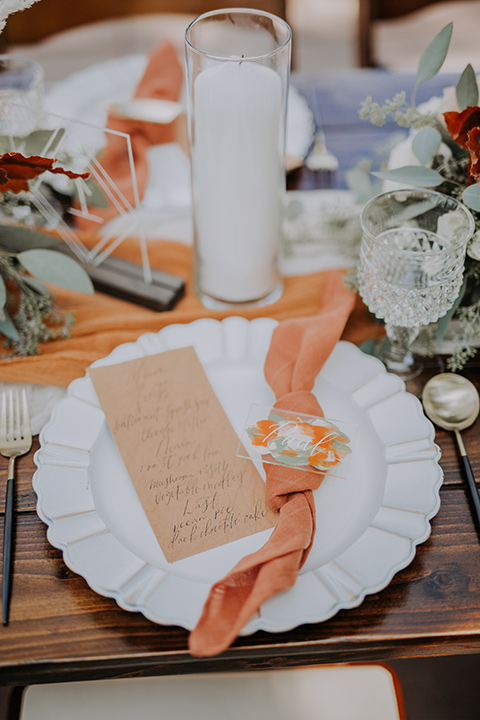 white plates with burnt orange linens and gold flatware