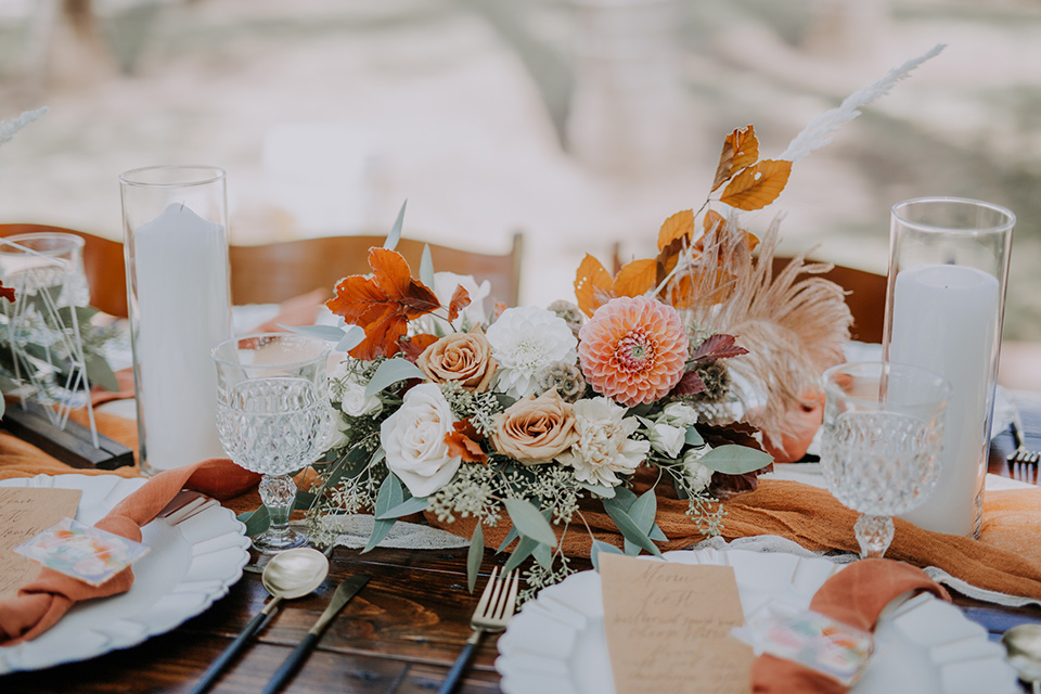 farmhouse table with white and burnt orange linens and gold flatware