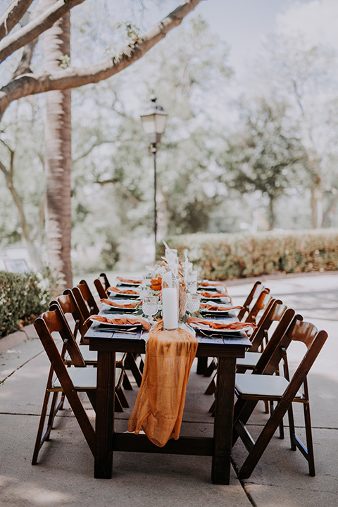 bride farmhouse table set up with white and orange linens and gold decor