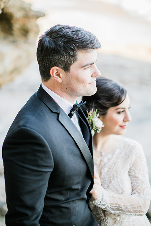 bride in a flowing gown with an illusion neckline and hair in a soft updo with a crystal pin detail and the groom in a black notch lapel tuxedo with a black bow tie holding his bride close