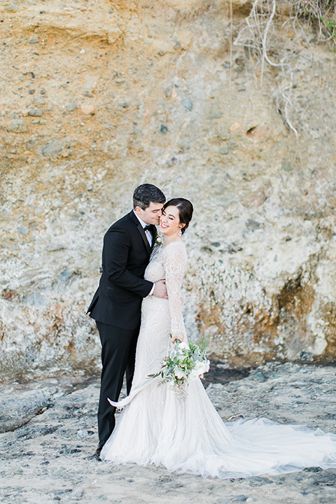 bride in a flowing gown with an illusion neckline and hair in a soft updo with a crystal pin detail and the groom in a black notch lapel suit with a black bow tie by the rock cliff
