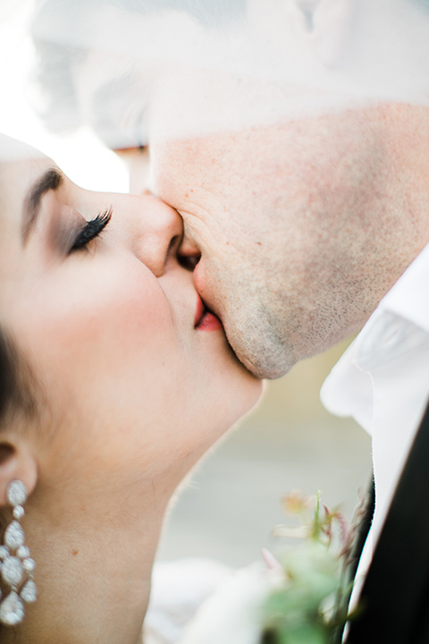 bride in a flowing gown with an illusion neckline and hair in a soft updo with a crystal pin detail and the groom in a black notch lapel tuxedo with a black bow tie kissing