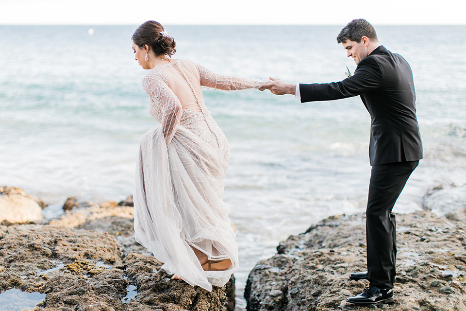 bride in a flowing gown with an illusion neckline and hair in a soft updo with a crystal pin detail and the groom in a black notch lapel tuxedo with a black bow tie holding hands