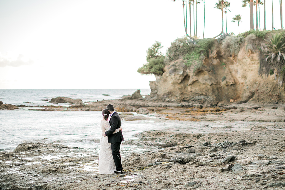 bride in a flowing gown with an illusion neckline and hair in a soft updo with a crystal pin detail and the groom in a black notch lapel tuxedo with a black bow tie on the rocks
