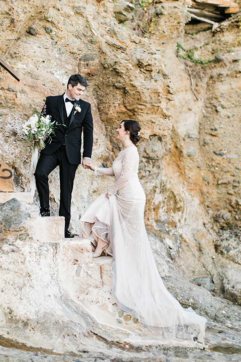 bride in a flowing gown with an illusion neckline and hair in a soft updo with a crystal pin detail and the groom in a black notch lapel suit with a black bow tie under veil