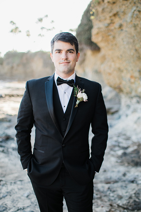 the groom in a black notch lapel suit with a black bow tie