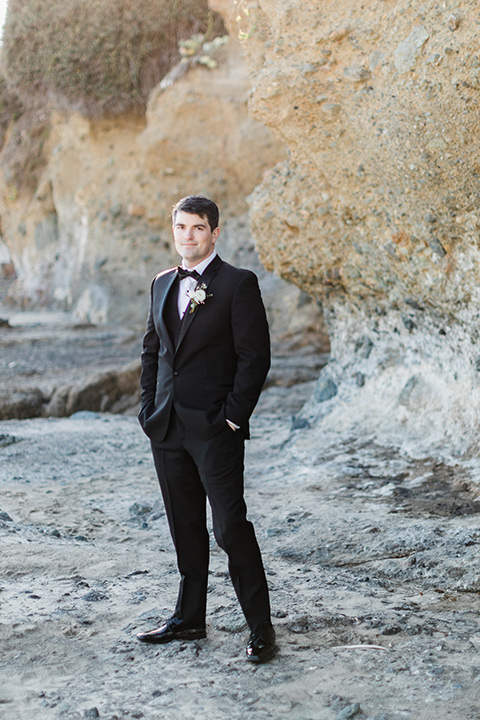 the groom in a black notch lapel tuxedo with a black bow tie
