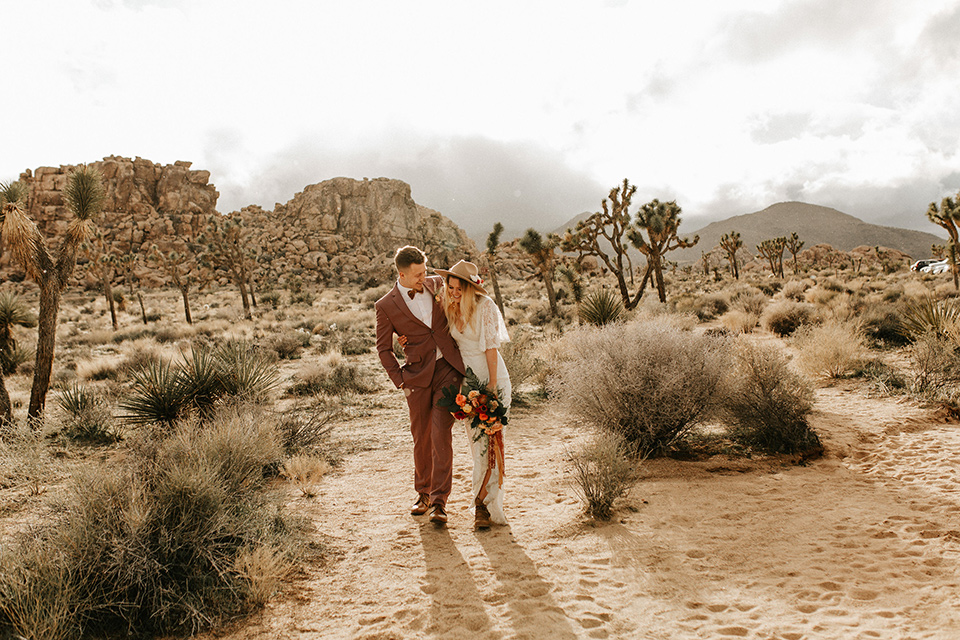 bride in a lace bohemian gown with flowing sleeves and wide brimmed hat and the groom in a rose pink suit with a tan long tie