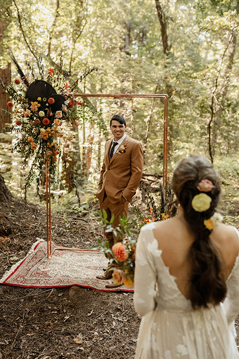 formfitting bridal lace gown with sleeves and the groom in a caramel suit with long tie