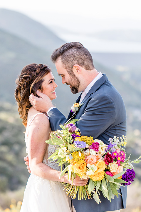bride in a lace gown with thin straps and beaded bodice, the groom in a blue suit coat and tan pants with a white long tie close together