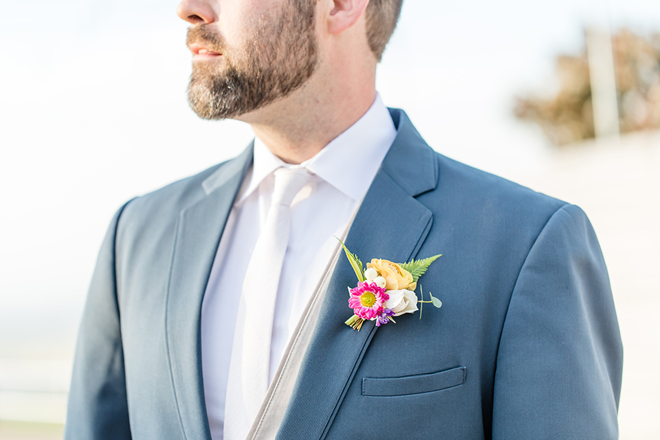 bride in a lace gown with thin straps and beaded bodice, the groom in a blue suit coat and tan pants with a white long tie