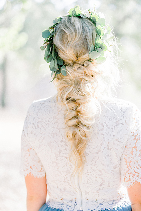 bride in a two-piece gown with a blue tulle skirt and white lace shirt and her hair in a loose French braid and floral crown