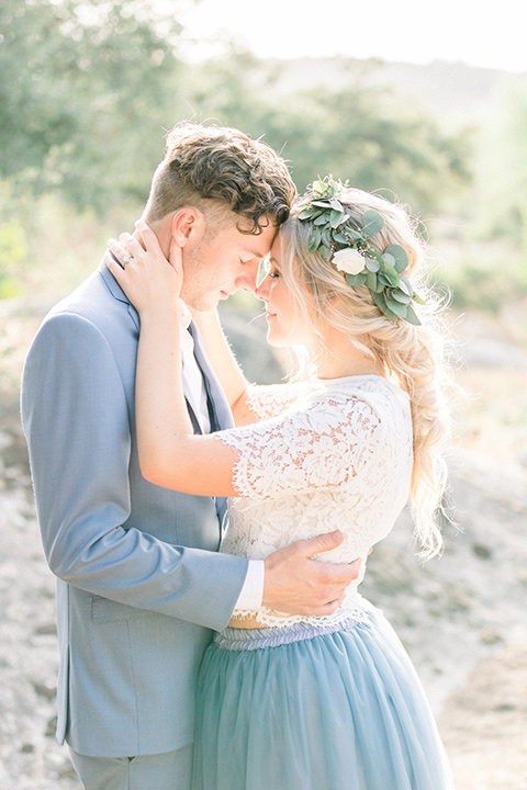 bride in a two-piece gown with a blue tulle skirt and white lace shirt and her hair in a loose French braid and floral crown the groom in a light blue suit with no tie and brown shoes