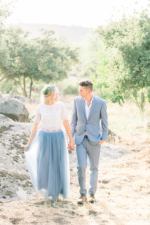 bride in a two-piece gown with a blue tulle skirt and white lace shirt and her hair in a loose French braid and floral crown groom in a light blue suit with no tie and brown shoes