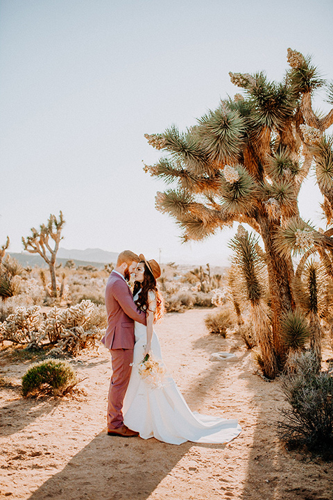 bride in a high neckline gown with lace details, groom in a rose pink suit with a bow tie