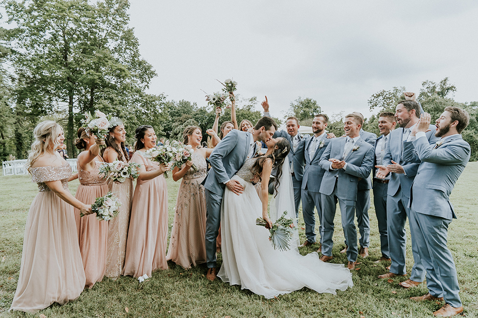 bride in a white ballgown with a high slit on the leg and v-neckline, the bridesmaids in light blush pink gowns, groomsmen and groom in light blue suits with long ties, all cheering
