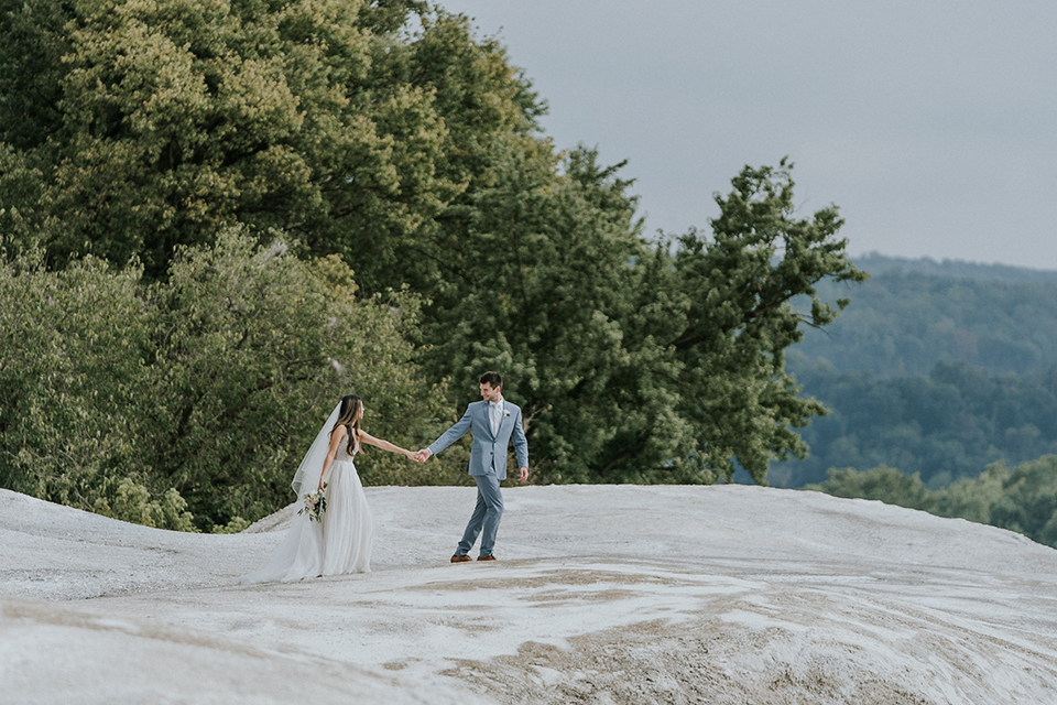 bride in a white ballgown with a high slit on the leg and v-neckline and groom in light blue suits with a long tie walking on a rock