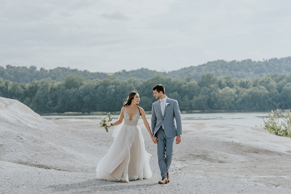 bride in a white ballgown with a high slit on the leg and v-neckline and groom in light blue suits with a long tie walking