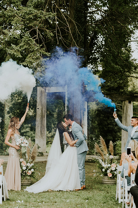 bride in a white ballgown with a high slit on the leg and v-neckline and groom in light blue suits with a long tie first kiss