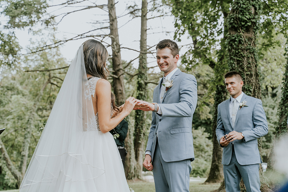 bride in a white ballgown with a high slit on the leg and v-neckline and groom in light blue suits with a long tie exchanging rings