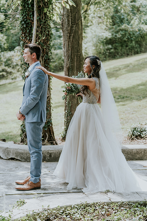 bride in a white ballgown with a high slit on the leg and v-neckline and groom in light blue suits with a long tie first look