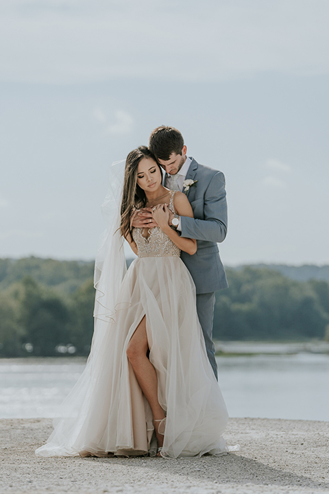 bride in a white ballgown with a high slit on the leg and v-neckline and groom in light blue suits with a long tie couple on top of rock