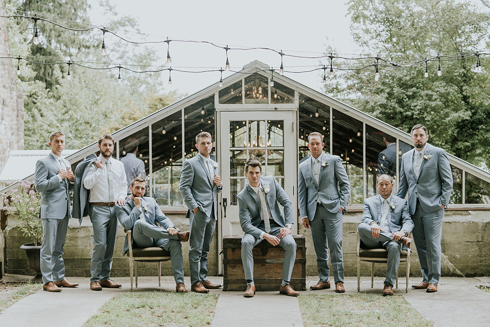 groomsmen and groom in light blue suits with long ties, all cheering