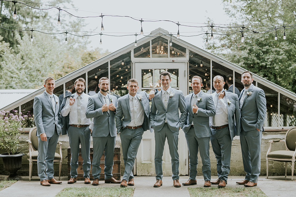 groomsmen and groom in light blue suits with long ties, standing