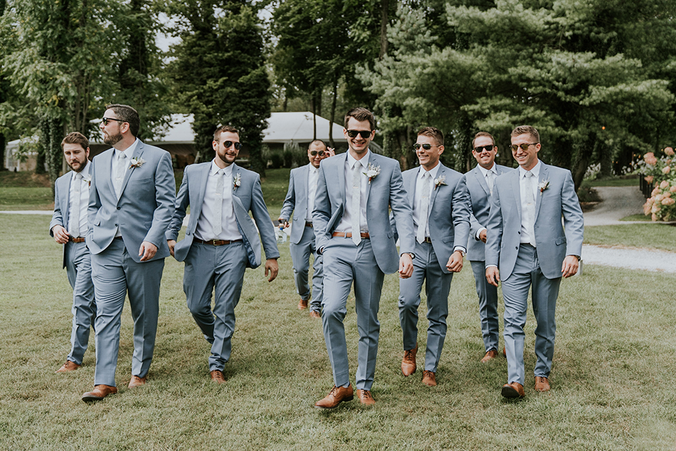 groomsmen and groom in light blue suits with long ties, walking
