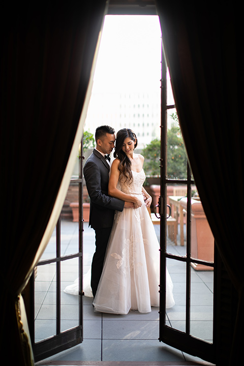 bride in a modern ballgown with a strapless neckline, groom in a charcoal grey suit with a black bow tie