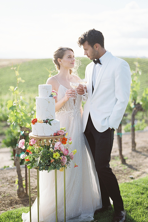 bride in a white flowing gown with a v neckline and the groom in a white dinner jacket and black pants
