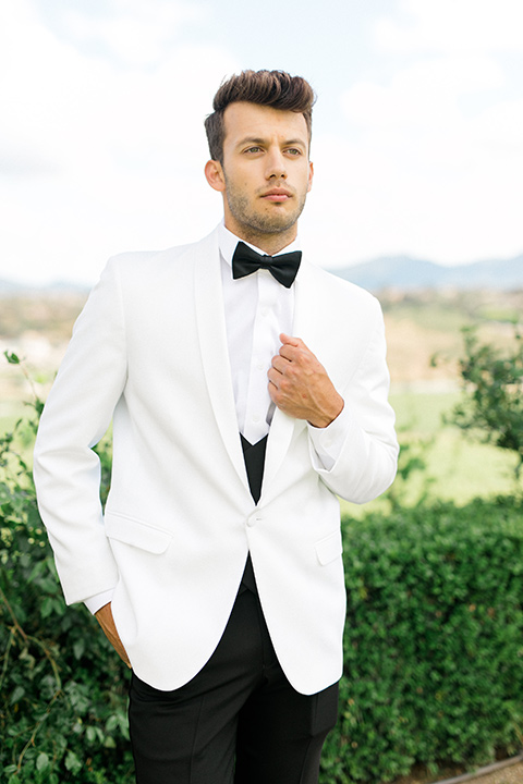 the groom in a white dinner jacket and black pants