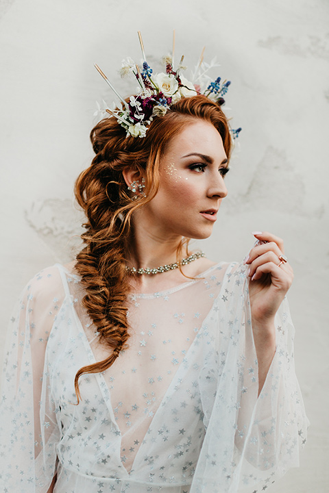 bride in an ivory lace gown with flowing sleeves and a braided hairstyle